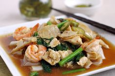 Rad Na recipe - is a Thai-Chinese noodle dish - fried rice noodles drenched in a savory sauce with seafood, meat, and vegetables Easy Asian Recipes, Thai Recipes, Easy Healthy Recipes, Seafood Recipes, Easy Meals, Cooking Recipes, Hawaiian Recipes, Rad Na Recipe, Chinese Noodle Dishes