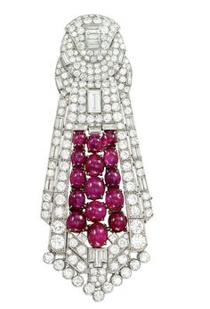ART DECO RUBY AND DIAMOND BROOCH  Of stylised epaulette form, the circular panel surmount with central baguette-cut diamond detail within a pav brilliant-cut diamond ground, to the widening lower section similarly set with a further rectangular-cut diamond accent and central cabochon ruby cluster, circa 1930, French marks for platinum, 10.7cm long.  Image: Christies