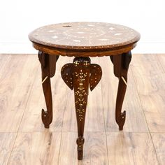 This side table is featured in a solid wood with a glossy mahogany finish. This boho chic end table has elephant and palm tree motifs on its top, floral motifs on its legs and scroll feet. A charming addition to any room! #bohemian #tables #endtable #sandiegovintage #vintagefurniture