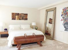 On the right of this eclectic white master's bed is a pressed-tin mirror from Hiden Galleries and an Eddie Martinez painting. Above the bed, an El Anatsui hanging is dressed in Restoration Hardware linens.