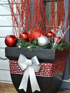 Festive front porch planter. . .Use big flower pots as a base and fill them with evergreen garland, huge ornaments, sparkly twigs and white lights.