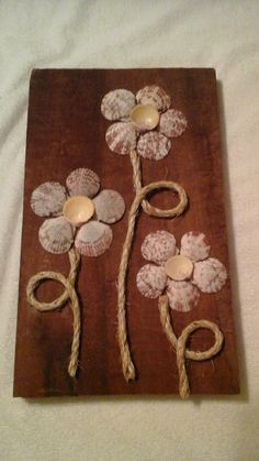 This is a 7 1 piece of reclaimed pine wood with a deep red finish from a year old house in Pasadena, MD. Mounted on the piece of wood are three flowers made of weathered rope for the leaves and stems and predominantly white pattern seashells found Sea Crafts, Rock Crafts, Diy And Crafts, Arts And Crafts, Decor Crafts, Recycled Crafts, Baby Crafts, Seashell Projects, Driftwood Crafts