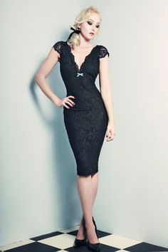 Our classic Fifi Dress is reimaged this season in a coquette summer style. Demi-sheer black lace dress is lined in seductive stretch power net to sculpt an hourglass silhouette. The deep v neckline defines a sweeping décolletage and is accented with coquette scallop lace edging. Trimmed cap sleeves and plush velvet bow at centre, the dress features centre back zip for ease of wear. Team with our sleek slim 50s belt to cinch the waist and step out in a truly romantic seasonal…