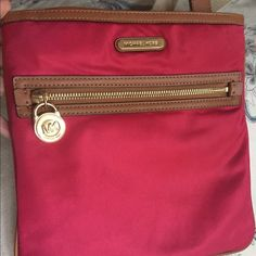 Michael Kors Nylon Crossbody Bag A beautiful red Crossbody bag with gold toned accents, can be dressed up or used with your favorite blue jeans! Perfect condition! Moving to Washington, so everything must go! ❤️ Michael Kors Accessories
