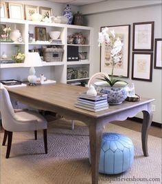 Grande table en bois faisant office de bureau et placée au milieu de la pièce, cadres au mur, pouf, orchidée contribuent à rendre l'ambiance féminine et inspirante.