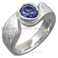 Mokume Swirl Engagement Ring with a Blue Sapphire - Mokume gently swirls around the center bezel set stone in this solitaire engagement ring. The sensual flow of the design works well with the organic pattern of the mokume. Wear it alone or pair it with a custom contoured wedding band. At the widest point, the band measures 5mm tapering to 3.5mm on the palm side. - White mokume gracefully swirls around a round blue sapphire in this designer ring.