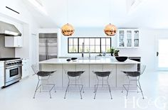 Black and white kitchen with rose gold bulb pendants over island and modern bar stools