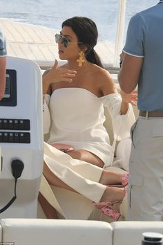 Golden girl: Kourtney later changed into a white mini dress and oversized gold earrings...