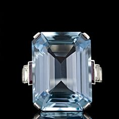 This magnificent, original Art Deco Aquamarine ring is one of the nicest we've seen. The 25.00 carat Aqua displays a crisp and refreshing swimming pool blue and is smartly presented in a classic Art Deco platinum setting with step-down ruby and diamond baguettes cascading down the shoulders. A gem of a cocktail ring from the 1930's.