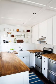 A CUP OF JO: {Jaw-dropping} Kitchen makeover. Love all the white, the open shelving, the butcher block countertops, the dark hardwood, the farmhouse sink! Home Kitchens, Builder Grade Kitchen, Kitchen Remodel, Kitchen Design, Kitchen Decor, Cabin Kitchens, New Kitchen, Assembled Kitchen Cabinets, Kitchen Interior