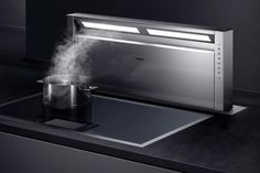 The Gaggenau 400 Series Retractable Downdraft Vent comes in two sizes and is positioned at the front of the cooktop. Contact Gaggenau directly for pricing on models and ordering information.