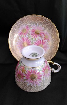 Beautiful teacup and saucer by Tuscan featuring hand painted pink daisies and an elaborate gilt honeycomb pattern. This much sought-after china service dates back to the late 1940s and very rarely comes on the market. This duo is in excellent condition for its age, with no chips,