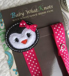 This is an adorable pacifier clip featuring a penguin on top. One end of the clip has a snap to loop around and attach to the pacifier and the