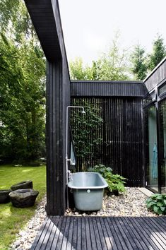 Outdoor bathroom with black slatted timber privacy panels
