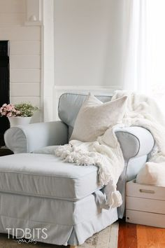 A light living room furnished with a light blue twoseat sofa with