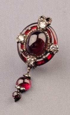Antique Garnet and Diamond Brooch, set with a carbuncle suspending smaller cabochons, set with four circular-cut diamonds with rose-cut diamond accents.: