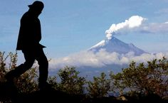 A man walks atop the crest of the Xilicatzi hill in Tlaxcala, Mexico with Popocatepetl volcano in the background. Photograph: Guadalupe Perez/AFP/Getty Images
