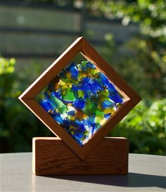 Color your sunny windowsill. This freestanding suncatcher measures 11 inches high, 10 inches wide, and 2 inches deep. The beautiful artist-made sea glass is loosely trapped between two plates of thick