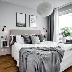 Schlafzimmer in Grau/Weiß mit kuschligen Decken und Bildern über dem Bett.