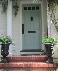 Love this front door color. The door color is Benjamin Moore Wythe Blue; door handle set is by Weslock; exterior paint color is unknown but is close to Benjamin Moore China White or Pratt and Lambert Gray Moire. House Of Turquoise, Exterior Paint Colors, Exterior House Colors, Exterior Shutters, Cottage Exterior, Benjamin Moore Colors, Whythe Blue Benjamin Moore, Benjamin Moore Historical Colors, Painted Front Doors