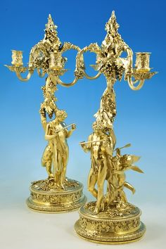 A Pash and Sons - Fine Antique Silver AN IMPORTANT PAIR OF GEORGE IV SILVER-GILT THREE-LIGHT CANDELABRA MARK OF PHILIP RUNDELL, LONDON, 1820, RETAILED BY RUNDELL, BRIDGE AND RUNDELL, BASED ON THE DESIGNS OF JOHN FLAXMAN, MODELLED BY EDWARD HODGES BAILY