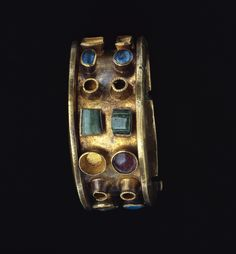 Roman bracelet, made of gold, glass, and emerald. AD 300-400. A heavy gold band elaborated by colored stones and glass forms this massive gold bracelet. The bracelet was made in two pieces, which were then hinged and secured with a pin decorated with green glass. The edges of the gold band are folded outwards at a perpendicular angle, forming a ledge that served to protect the stones. Blue, green, and red glass; emeralds; and now-missing pearls were placed in pairs...
