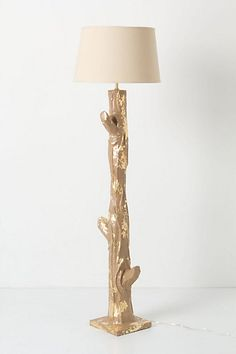 Gilded Bark Floor Base #anthropologie. A towering tree trunk, constructed of papier mache and glinting gold leaf, sprouts from plush carpet and hardwood floors. Handmade by Stray Dog Designs.