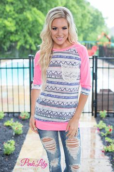 This gorgeous 3/4 sleeve blouse is perfect for those cooler days! This hot pink baseball style tee is easy to pair with jeans or jeggings for a relaxed look! It also has bold aztec style print in off-white, purple, and hot pink on the main panels of the shirt and on the cuffs of the sleeves for a cute accent! The finishing detail of the lace pocket is so gorgeous, too!