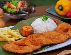 """Cutlet """"Valluna"""", a typical dish of the Valle del Cauca region of Colombia and the Afro-Colombian culture of the area near the Watermelon Ocean. It includes a milanesa, usually prepared with a lean pork loin. Beef or chicken can also be used. Traditional accompaniments include rice, sliced tomatoes, onions, chopped fried plantains or fries and a drink called """"Lulada"""" made with lulo fruit, water and sugar"""