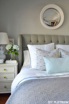 Gray tufted headboard paired with white bedding and light blue accents. Makes for a calming master bedroom.