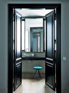 Peindre ses portes en noir brillant et ponctuer l'ambiance d'une couleur vive dans le champ de vision.