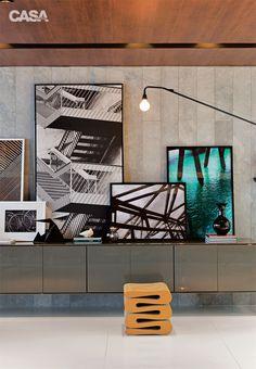 """Encaixe esperto. No projeto de Eliane e Laís Kruschewsky, a luminária da Vitra tem dupla função. """"Além de formar um desenho entre as fotografias emolduradas, ilumina as imagens sobre o aparador"""", especifica Eliane."""