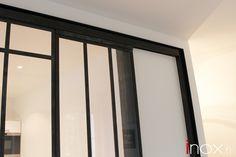 Fenêtre d'atelier acier brut avec porte coulissante intégrée.