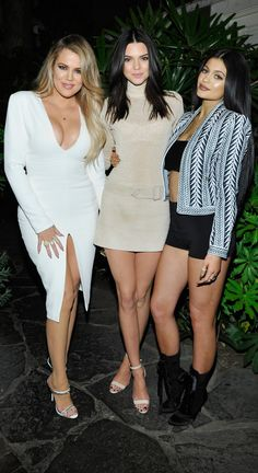 Khloe Kardashian wearing a white bodycon dress with a leg slit, Kendall Jenner wearing a sparkling neutral turtleneck and belted miniskirt, and Kylie Jenner wearing a revealing Balmain ensemble at the Opening Ceremony x Calvin Klein party.