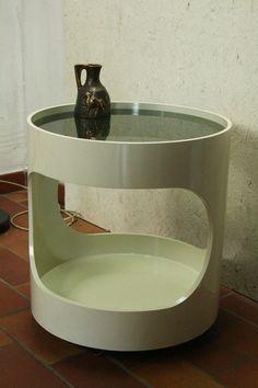 This side table was designed during the 1970s and manufactured by Opal Möbel in Germany i believe part of their Luna series. It is made from white plastic ,well yeah its the 70s,and features a tinted glass top and coasters or wheels on the bottom. Both glass and plastic in good condition with little signs of wear.Hey but its vintage and not new.   49cm high and roughly 45 across ..   102216
