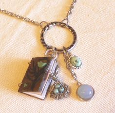 Miniature bird book & charms: wire wrapped nest w/ beads, moonstone, turquoise.  Book features antique birds and quotes: It is the beautiful bird that gets caged --Chinese Proverb.  Silver chain