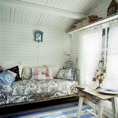 lovely antique iron daybed, white wood clapboard, vaulted ceiling and sweet little shelf.  love the metal flowers on the table in front of the window ...boho cottage-y sweet