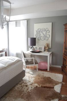 Amazing bedroom with grey walls, West Elm parsons Desk in Glossy White, pink leather Moroccan leather pouf, mercury glass lamp, brown cowhide rug layered over cream flokati rug and Etsy Southern Nest Wooden Monogram. Martha Stewart Flagstone Paint Color