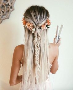 fishtail hairdo. Half down half up hairdo. She is also wearing flowers. Festival inspired hairstyle for a bohemian outfit.