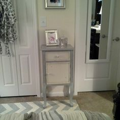 Bedroom accent cabinet with silver hardware and mirrored picture frame