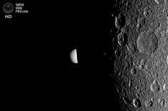 Мимас, выглядывающий из-за тёмной стороны Дионы. (NASA/JPL-Caltech/SSI)