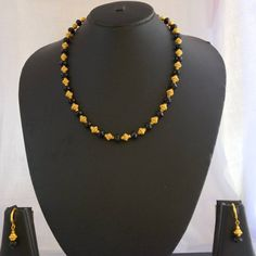 This is a short necklace with golden and black beads. A pair of matching earrings is provided. Pendant Jewelry, Beaded Jewelry, Beaded Necklace, Gold Jewelry, Pearl Necklace, Short Necklace, Necklace Set, Gold Mangalsutra, Mangalsutra Design