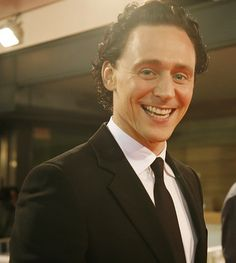 Tom smiling for the camera outside his hotel while wearing a black suit and tie.