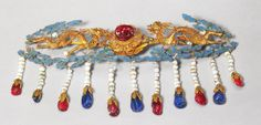 Jeweled gold, kingfisher feather, pearl, ruby, and tourmaline hair ornament, Qing Dynasty, on display in the Forbidden City Palace Museum collection.