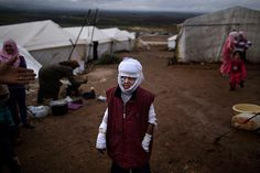 Abdullah Ahmed, 10, who suffered burns in a Syrian government air strike and fled his home with his family, stands outside their tent at a camp for displaced Syrians in the village of Atmeh in December 2012