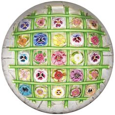 Parabelle Glass 1998 chequer paperweight, with an assortment of thirteen pansy canes and twelve rose canes, divided by green cables on white upset muslin. Signed/dated. Artist proof. Diameter 3 3/8""