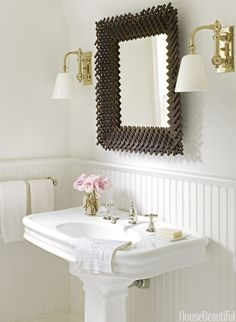 Robert Stilin - Chic cottage powder room features basketweave mirror flanked by Pimlico Sconces in Antique Burnished Brass over pedestal sink against a backdrop of white beadboard.