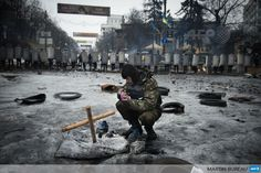 UKRAINE, Kiev : An anti-government protester lights a candle in front of riot police forces in Kiev, on February 13, 2014. Ukraine has been in chaos since November when President Viktor Yanukovych ditched an EU trade and political pact in favour of closer ties with Moscow, its former Soviet master. AFP PHOTO / MARTIN BUREAU