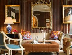 Beeline Home - Bunny Williams. Are the walls corrugated metal? Nice palette. Camel ottoman, cream studded sofa, blue accent chair and ikat pillows. Gilded faux bois mirror is stunning.
