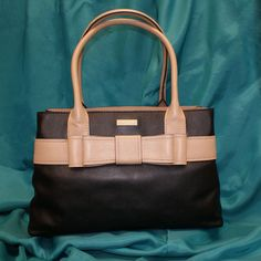 """""""Winning with Spades,"""" a Kate Spade handbag; black leather with tan trim and double bow; zippered divider and inside pocket; pockets for cell phone; cream lining with black polka dots"""